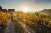 Sunrise In Countryside Landscape. Fields And Countryside Landscape. Old House In Nature In Sunrise.  poster