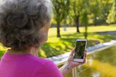 Old Lady Talking To Daughter Through Video Call While Walking In Park. Senior Grey Haired Woman In C poster