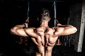 Back Muscles, Young Strong Man Workout Training Back Muscles In The Gym Dark Image poster