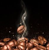Roasted coffee beans. Seeds of freshly roasted coffee with smoke. Coffee beans closeup with emphasis poster