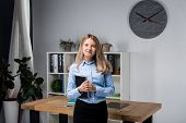 Businesswoman Holding Large File. Young Womanl Standing In The Office And Holding Folder. Portrait O poster