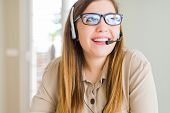 Beautiful young operator woman wearing headset at the office smiling looking side and staring away t poster