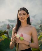 A Beautiful Woman In Traditional Thai Northern Traditional Costume Stand In Pink Lotus Pond , Identi poster
