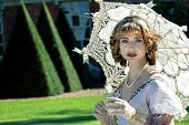 Beautiful Woman In Vintage Clothing Sitting On Lawn In Front Of Stately Home Holding Parasol And Dri poster