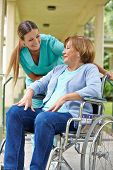 Elderly patient in wheelchair talking to nurse in a hospital garden