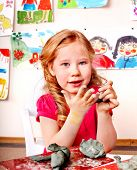 stock photo of molding clay  - Child girl with clay in play room - JPG