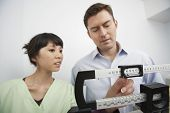 Man measuring weight with doctor adjusting scale