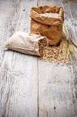 foto of roughage  - Oat flakes spilling from the burlap bag on old wooden table - JPG