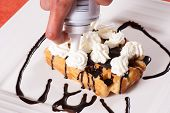 foto of whip-hand  - Hand decorating a waffle with whipping cream - JPG
