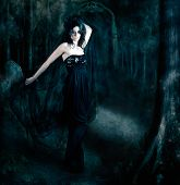 stock photo of evening gown  - Moody atmospheric portrait of an elegant mysterious woman posing in a black evening gown amongst the shadows of darkness - JPG