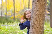 Autumn forest with child girl greeting hand behind poplar tree trunk