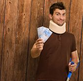 stock photo of neck brace  - Disabled Man With Neck Brace Holding Euro Note On Wooden Background - JPG