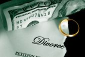 stock photo of divorce-papers  - torn divorce decree and cash with wedding ring - JPG