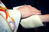 foto of priest  - Catholic priest holding his hand on newlyweds