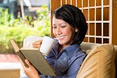 Student - Young asian woman or girl sitting on a sofa with a cup of coffee reading a book, she is le