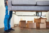 pic of sofa  - Close Up Of Man Carrying Sofa As He Moves Into New Home - JPG