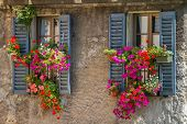 stock photo of geranium  - Vintage windows with open wooden shutters and fresh flowers - JPG