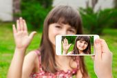 Female Hand Holding A Phone With Video  Of Little Girl On The Screen