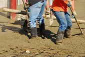 pic of concrete pouring  - Workers pouring a concrete pad outside a new commercial building - JPG