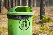 stock photo of dustbin  - Green trash basket with sign pictogram in forest - JPG