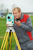 image of theodolite  - One surveyor worker working with theodolite transit equipment at spring field construction site outdoors - JPG