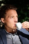 pic of down jacket  - Handsome man portrait drinking espresso at cafe enjoying coffee - JPG