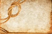 stock photo of manila paper  - Grunge texture of old book paper sheet and hemp rope with space for your text - JPG