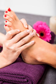 stock photo of stimulating  - Woman having a pedicure treatment at a spa or beauty salon with the pedicurist massaging the soles of her feet with a pumice stone to cleanse dead skin and stimulate the tissue - JPG