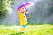 image of rainy season  - Funny cute curly toddler girl wearing yellow waterproof coat and boots holding colorful umbrella playing in the garden by rain and sun weather on a warm autumn or sumemr day - JPG