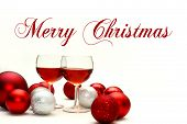 stock photo of sparkling wine  - Two wine glasses filled with red wine sit on an isolated white background with words Merry Christmas surrounded by silver and red sparkling Christmas Bulb Decorations - JPG