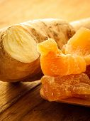 stock photo of home remedy  - Closeup dried candied crystallized ginger pieces and fresh root on wooden table - JPG