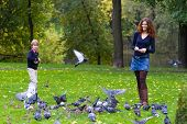stock photo of feeding  - Mother And Son Feeding Pigeons In A Park - JPG