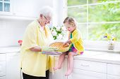 stock photo of granddaughter  - Happy beautiful great grandmother and her adorable granddaughter curly toddler girl in colorful dress baking an apple pie together standing next to white oven in sunny modern kitchen with big window - JPG