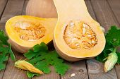 stock photo of butternut  - Two halves of butternut squash with green leaves on wooden table - JPG