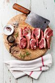 stock photo of cumin  - Raw fresh lamb ribs with salt pepper and cumin and meat cleaver on wooden cutting board on blue background - JPG