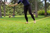 picture of nylons  - Lady practising slack line in the city park - JPG