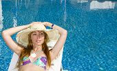 Woman Smiles In Straw Hat Having A Rest At Pool