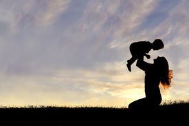 stock photo of headings  - A silhouette of a happy young mother laughing as she plays with her toddler child and lifts him over her head outside isolated against the sunset - JPG