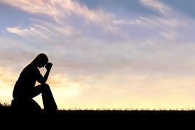 stock photo of prayer  - A silhouette of a young Christian woman is bowing her head in prayer and desperation outside during sunset - JPG