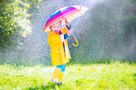 foto of rainy season  - Funny cute curly toddler girl wearing yellow waterproof coat and boots holding colorful umbrella playing in the garden by rain and sun weather on a warm autumn or sumemr day - JPG