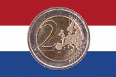 image of common  - Common face of two euros coin isolated on the national flag of Netherlands as background - JPG