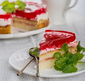 image of tort  - a piece of strawberry cake jelly on white background decorated with fresh roses and mint leaves - JPG