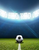 stock photo of illuminating  - A soccer stadium with a marked green grass pitch with a soccer ball on the centre mark at night under illuminated floodlights - JPG