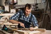 stock photo of carpentry  - Young craftsman in uniform working at carpentry  - JPG