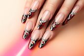 stock photo of nail-design  - Female hand with manicure and beautiful design on nails.