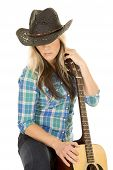 pic of cowgirls  - A cowgirl in her western hat looking down holding on to her guitar - JPG