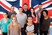 stock photo of united we stand  - Happy Group Of Diverse Students Standing In Front Of Uk Flag
