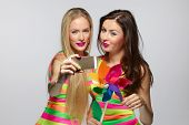 stock photo of two women taking cell phone  - Two girls friends with colorful clothing and makeup taking selfie with smartphone - JPG