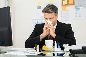 stock photo of blowing  - Mature Businessman At Office Desk Blowing His Nose - JPG
