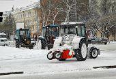 Постер, плакат: Tractors with snowplowing equipment on streets